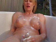 Tranny toys her cock in the bath