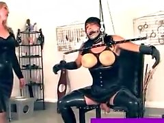 Crossdressing sissy facing a dominatrix
