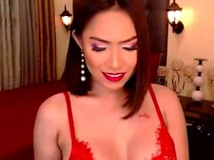 Festive Tranny in red lingerie playing hard to get